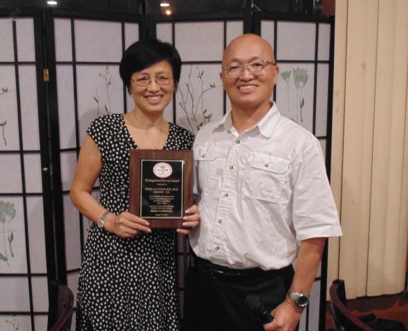 林义顺代表校友会向卸任会长郑榕岚博士赠送奖牌,表样她四年来对校友会的贡献