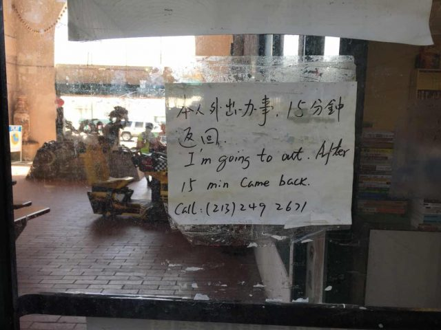 中午,唐人街一家小商铺门前的告示牌